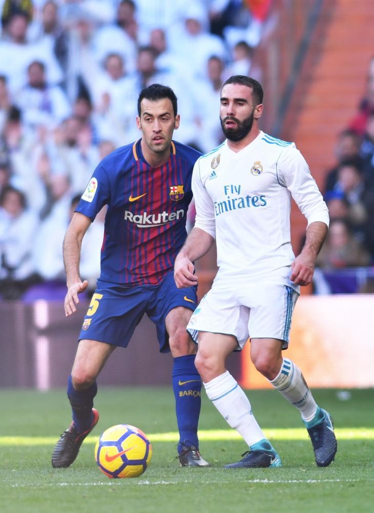 Dani Carvajal (Real Madrid) y Busquets (FC Barcelona) en accion durante el partido de Liga 2017/2018 entre Real Madrid y F.C. Barcelona (0-3) disputado en el Estadio Santiago Bernabéu de Madrid, 23/12/2017